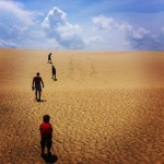 Four people wandering up a large sand dune with a blue sky and some clouds.