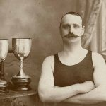 An old time strongman with a handlebar mustache in front of some trophies.